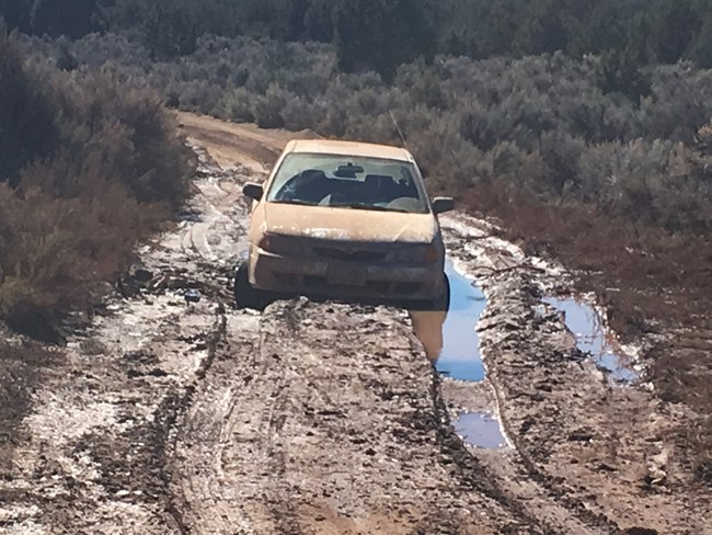 Car stuck in deep water and mud on an unpaved road