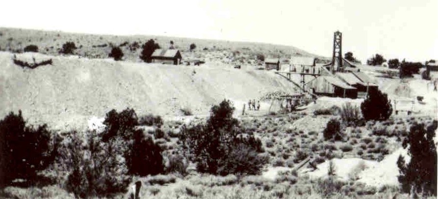 Image taken in 1917 showing several mine workers, a 100 foot long pile of rocks and several mine buildings