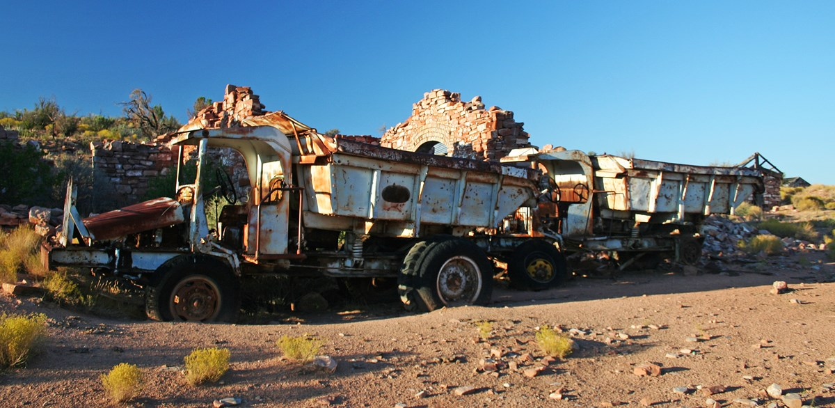 Two abandoned dump trucks in front of a ruin of a brick mine building