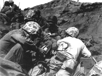 Navy corpsmen tending to wounded Marine