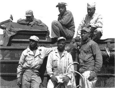 Marines pose with Army DUKW amphibious trucks