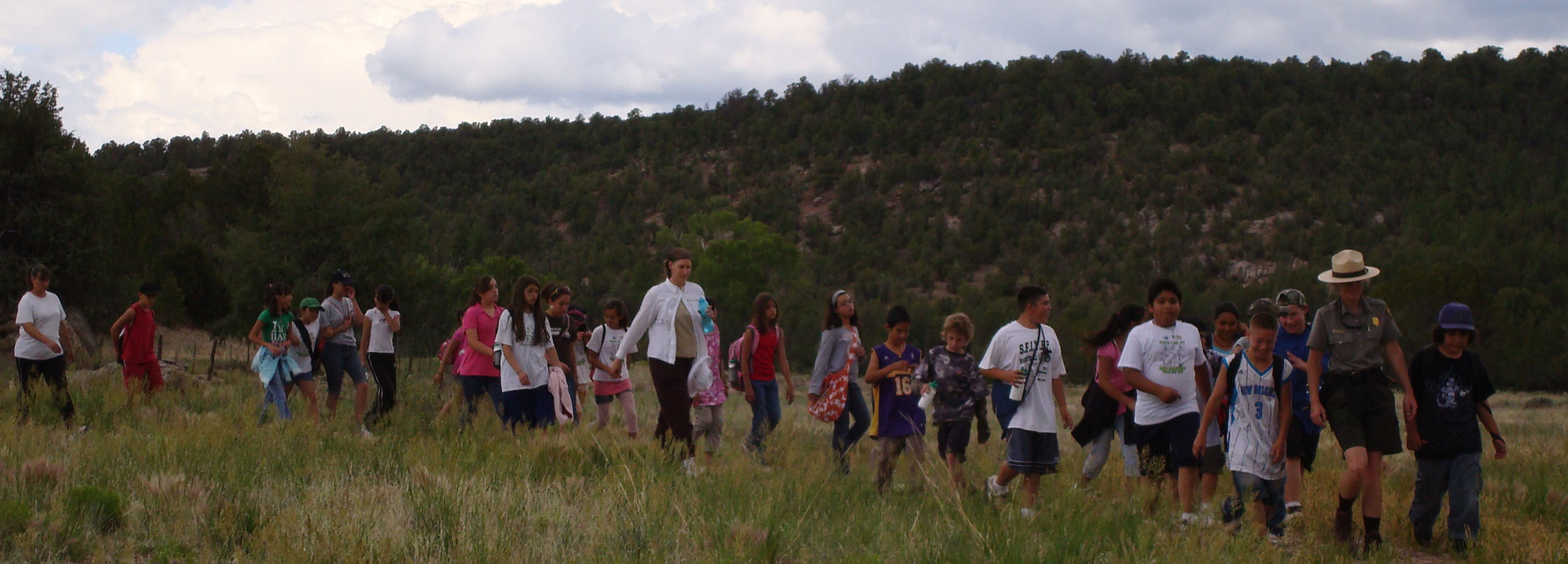 Large school group hiking to site with ranger leading