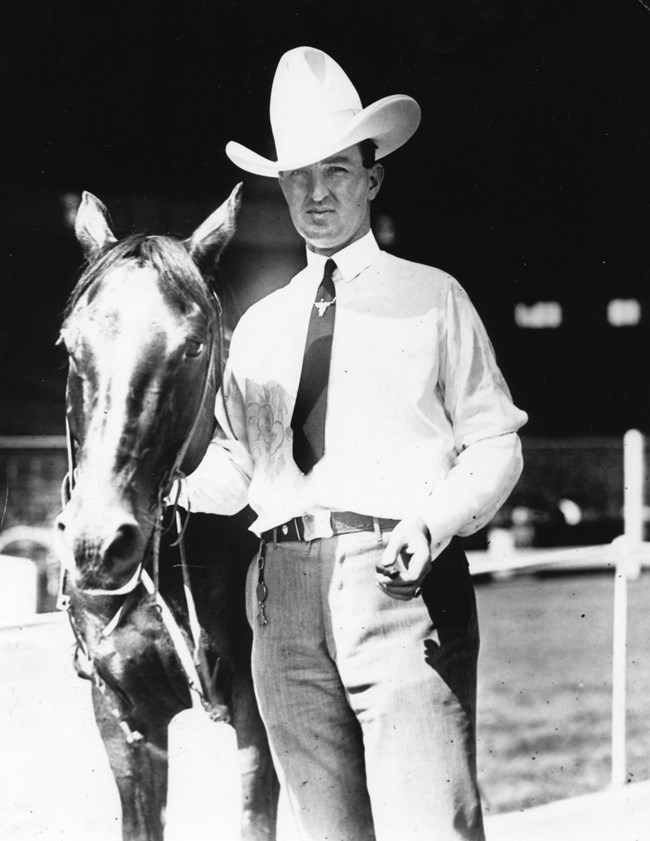 Man with cowboy hat standing next to a horse