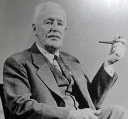 White-haired man wearing suit and holding pipe in formal portrait