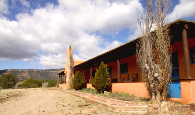 Side view of large ranch house with mesa in background