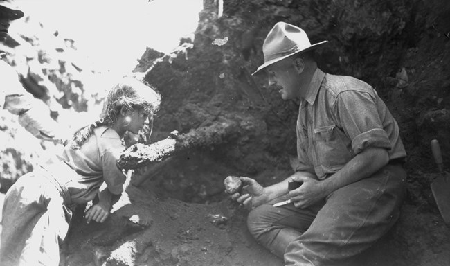 man and young girl looking at pot sherd