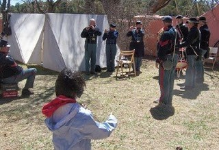 Back view of little girl in foreground who is gesturing as if conducting with fife and drum players in background