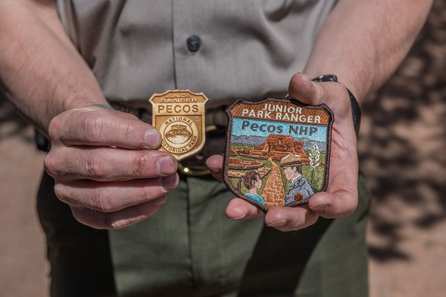 wooden badge and patch held in park rangers hands