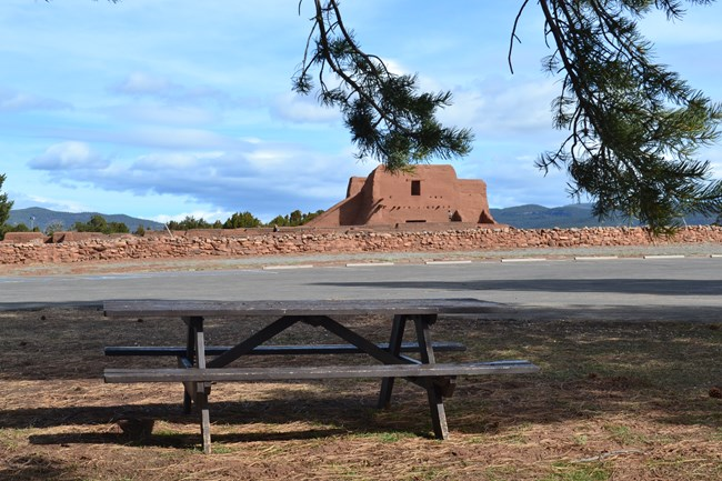 A picnic table with the remains of an old building in the background.