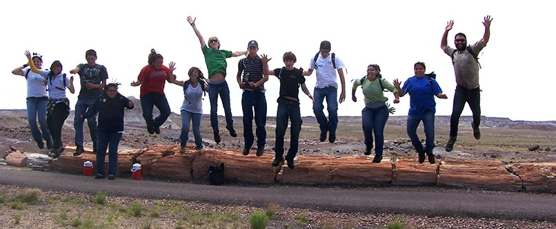 YCC crew members leap off petrified log