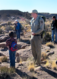 Park volunteer points out something to young visitor