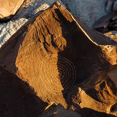 Sunlight moves across a spiral petroglyph during summer solstice at Martha's Butte