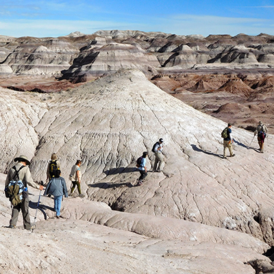Hikers crossing badlands in the Red Basin area
