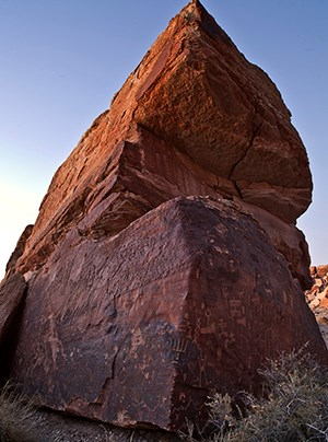 towering rock covered in petroglyphs on two sides