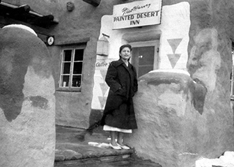 Young woman in long black coat stands outside lunch room door under sign reading Painted Desert Inn