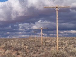 straight line of historic telephone poles under monsoon thunderheads