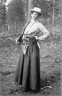 woman in long skirt holds gun over her shoulder