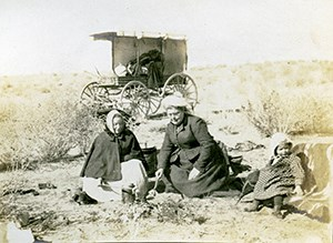 Two women and a baby picnic on the ground in front of a wagon