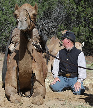 camel reenactor in period uniform sits next to a camel