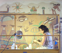 Flavia Benato works on a Kabotie mural in the dining room