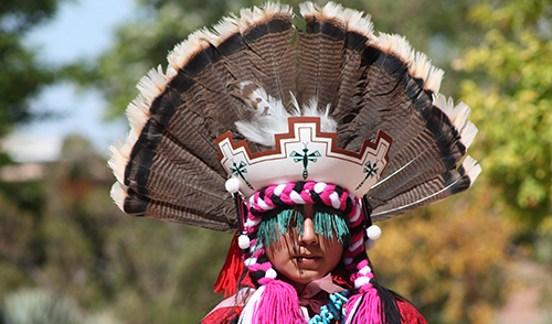 zuni dancer in elaborate feather headress