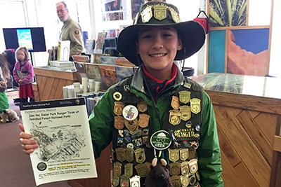 Junior Ranger Tigran shows off his badges and certificate