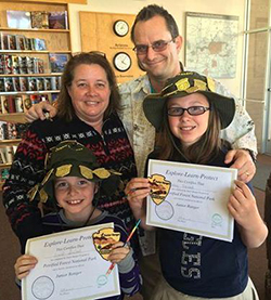 A family with 2 kids holding up Jr Ranger certificates