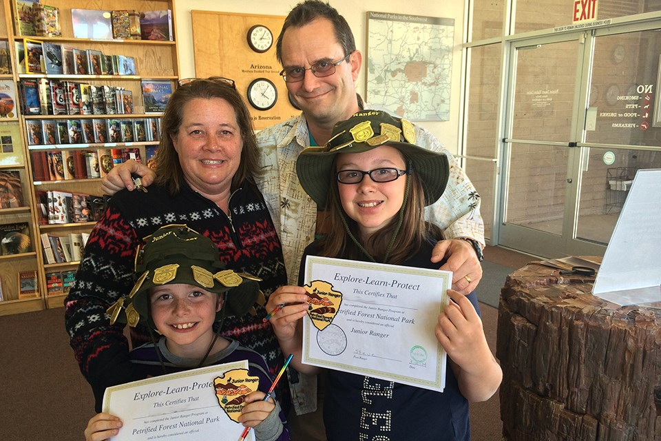 Two kids and their family show off their junior ranger certificates and badges