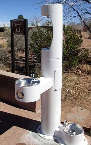 tall white water fountain with faucet at waist high and groundlevel