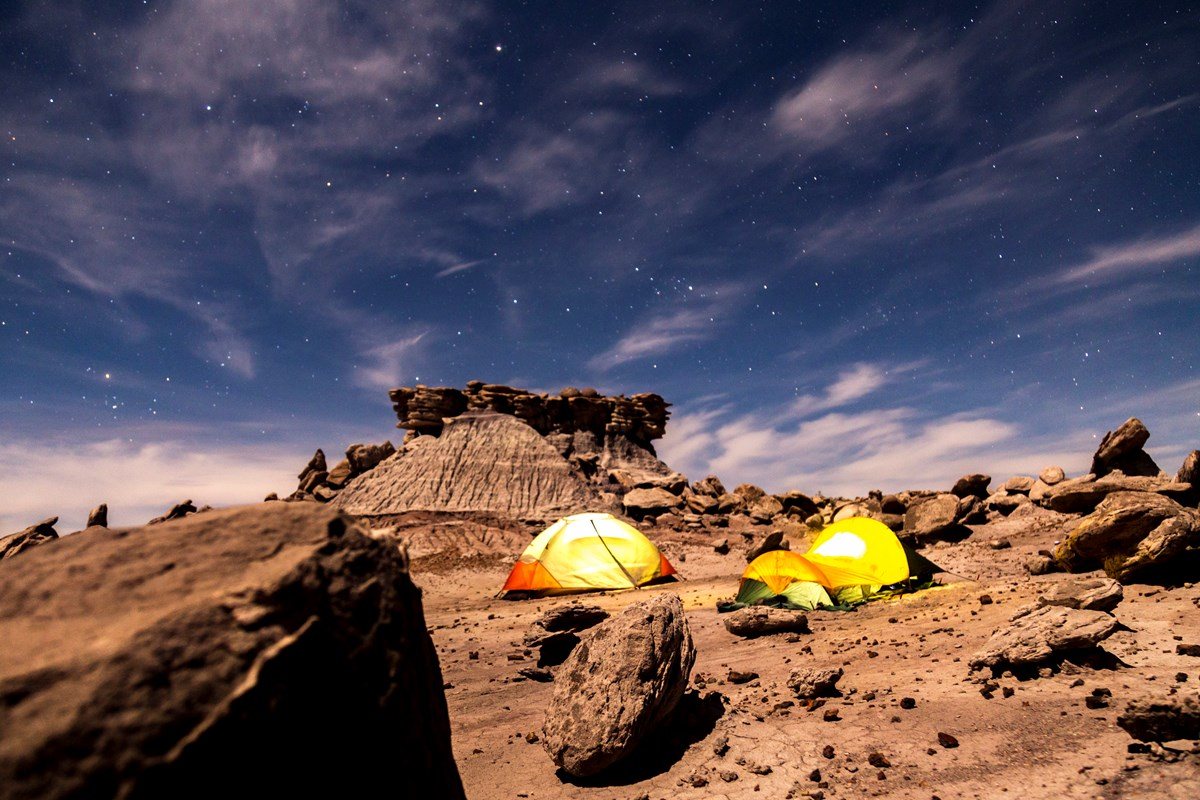 Two tents rest under starry skies among boulders and buttes in Devil's Playground.