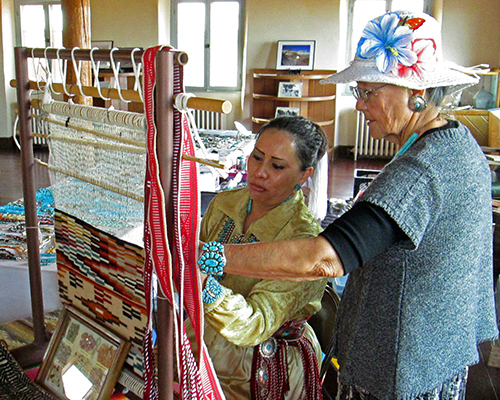 Alice and Angeline weaving on a traditional Navajo loom