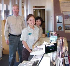 Charles, Marie, and Jin Hewett work as volunteers at the visitor center desk.
