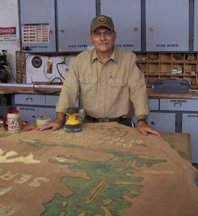 Paul Cox works on large, wooden NPS Arrowhead