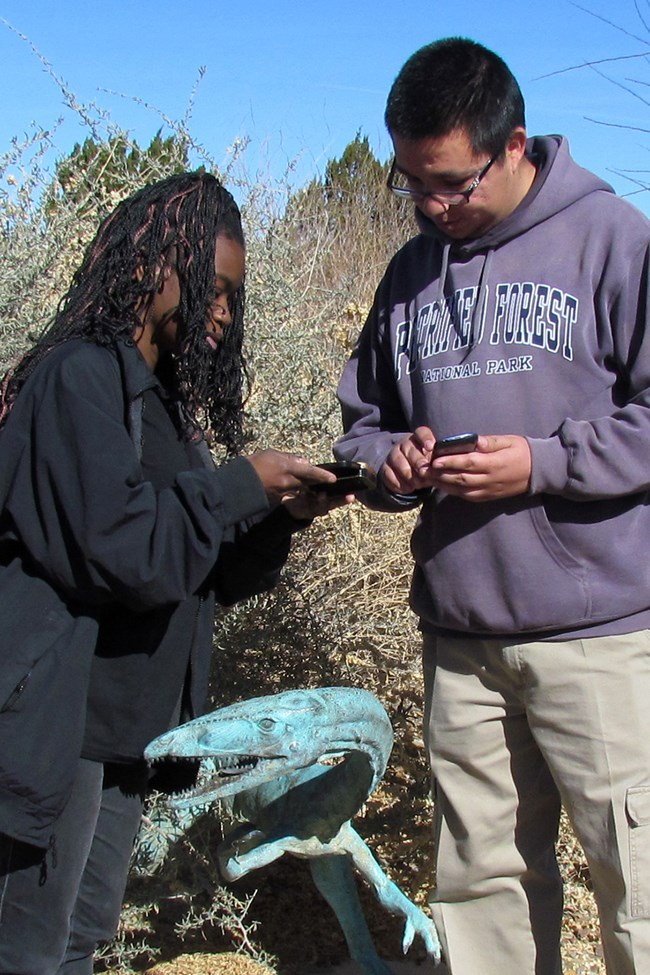 Two people geocaching, looking into a cache