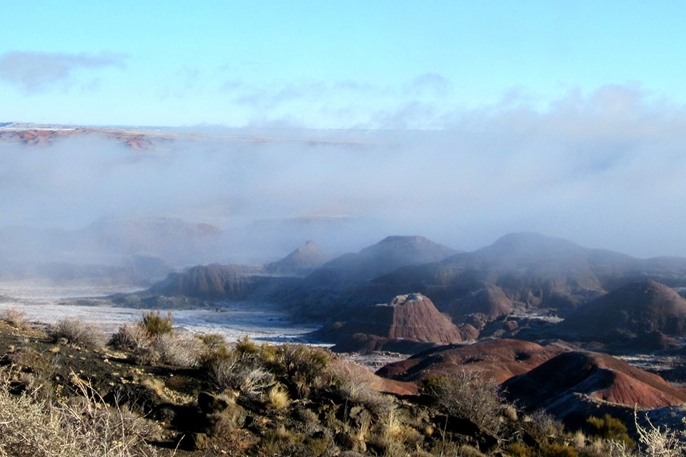 An inversion layer sends mist through the red badlands of the Painted Desert