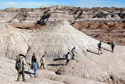 Backcountry hikers amidst color badlands.