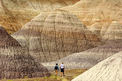 Two visitors walk the trail among the badlands at Blue Mesa