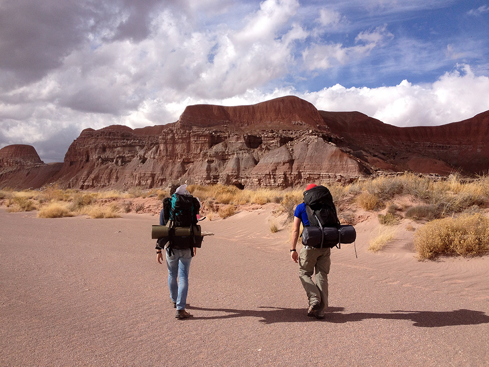 backpackers in wilderness area wash with red badlands