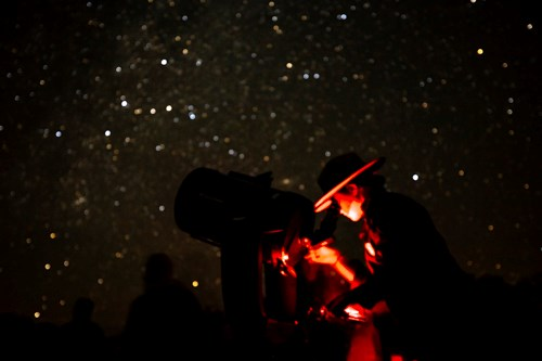 Illuminated in red light, a Park Ranger looks into a telescope while stars fill the background.