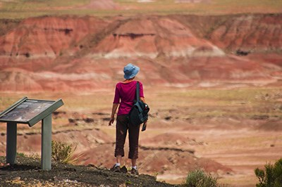Woman enjoys the view of the red Painted Desert from the Rim Trail