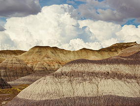 puffy clouds over badlands with distinct banding