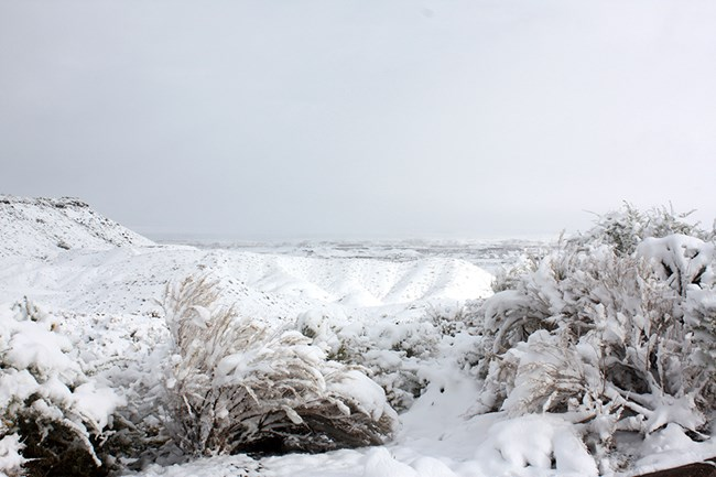 Snow covers badland hills in the Painted Desert