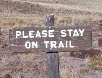 wooden sign asking visitors to Please Stay on Trail