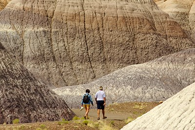 Hikers on the Blue Mesa Trail among colorfully banded badlands