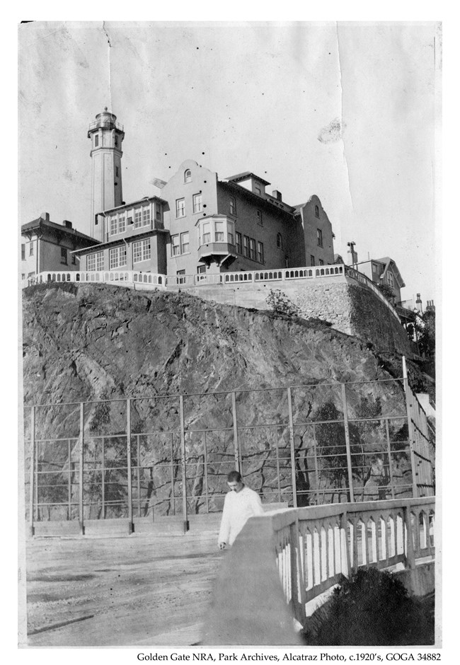 Alcatraz photo c1920s prisoner in all white walking on parade ground below comandants house and light house