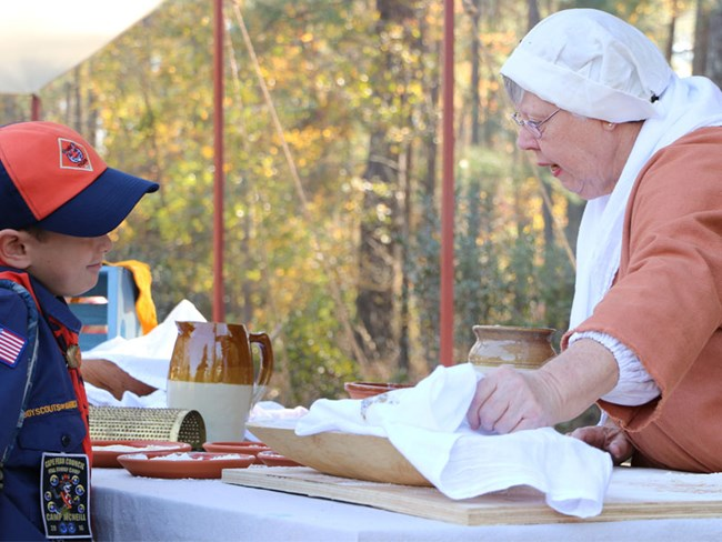 A woman in Colonial clothing shows historic foods to a Boy Scout