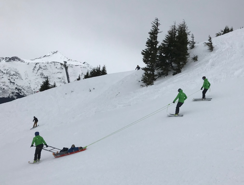 Three rangers carefully transport a patient in a sled down a ski slope.