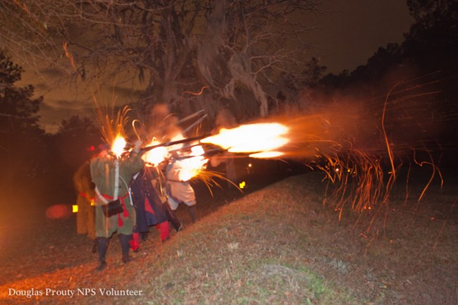 Patriots fire muskets, illuminating them on a dark night.