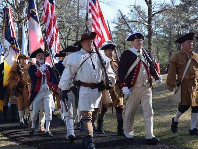 Revolutionary War reenactors march with flags