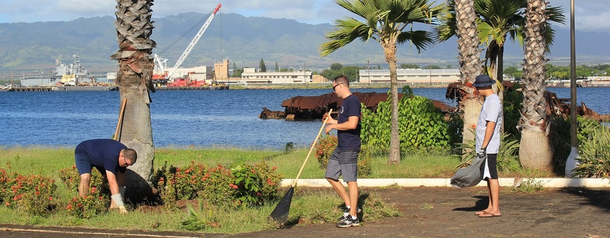 Members of the Coast Guard clean up the area around the USS Utah Memorial.